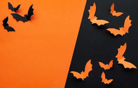 Black and orange paper bats flying over black and orange Imagens