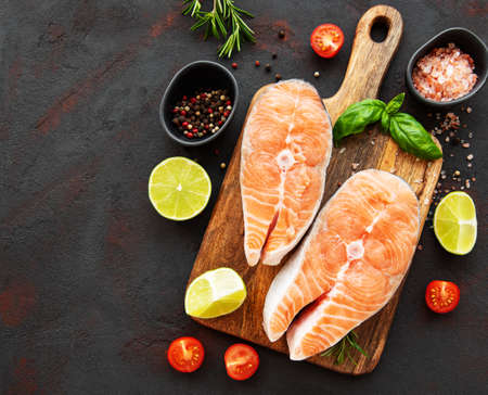 Raw salmon steaks and ingredients on a black slate board Stockfoto
