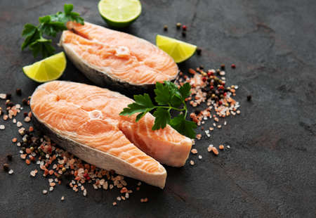 Raw salmon steaks and ingredients on a black slate board Фото со стока - 129815040