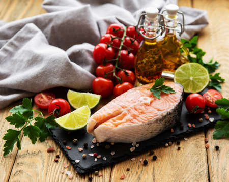 Raw salmon steaks and ingredients on a old wooden table Фото со стока - 129815041