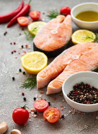 Raw salmon steaks and ingredients on a grey concrete background Фото со стока