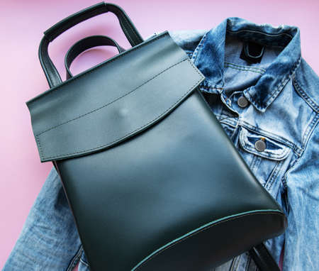 Green leather backpack and womens clothing, flat lay