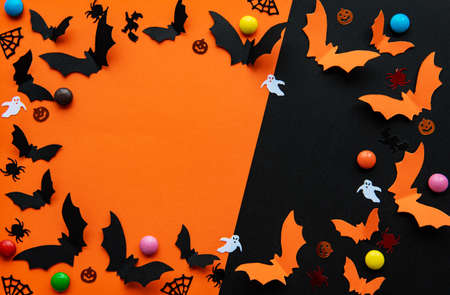 holidays  concept - halloween paper decorations and sweets with blank copy space over  orange and black background