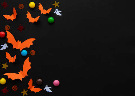 holidays  concept - halloween paper decorations and sweets with blank copy space over black background Stock fotó