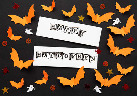 halloween  concept - orange paper bats and decorations flying over black background