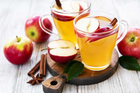 Cidre de pomme avec des bâtons de cannelle sur une vieille table en bois