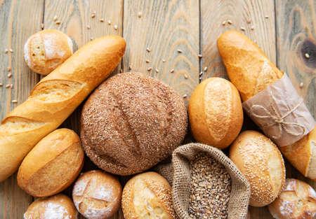 Auswahl an gebackenem Brot auf weißem Holzhintergrund