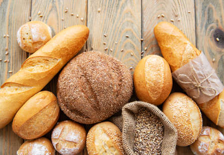Surtido de pan horneado sobre fondo blanco de madera