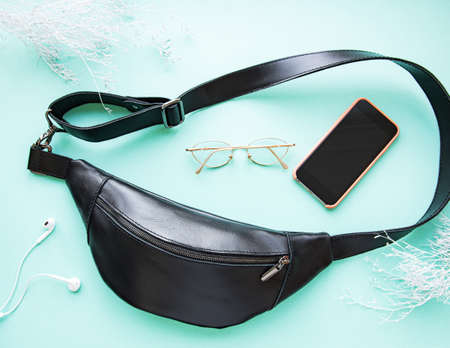Flat lay composition of black waist bag, phone and glasses on mint background 版權商用圖片