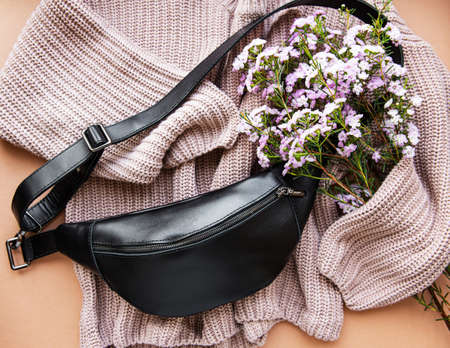 Flat lay composition of black waist bag, sweater and flowers on brown background 版權商用圖片