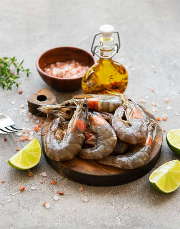 Fresh raw  prawns and spices on  grey concrete background Фото со стока