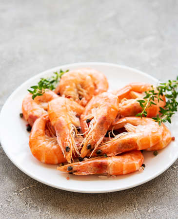 Shrimps in plate on a grey concrete background Фото со стока