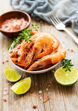 Shrimps served with lemons and spices on a old wooden table Фото со стока