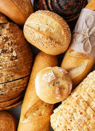 Assortment of baked bread on white wooden background Stock fotó