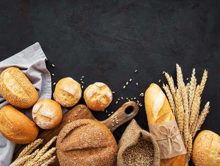 Assortment of baked bread on black concrete background