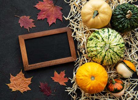 Pumpkins  on a black background with straw and blackcoard. Pumpkin harvest. Seasonal vegetables