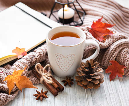 Autumn composition. Cup of tea, women fashion sweaters, dried leaves and notebook. Autumn, fall concept. Banco de Imagens
