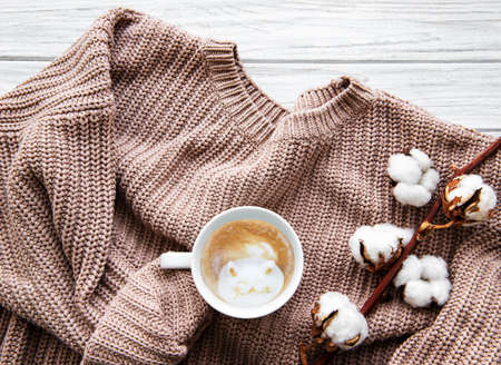 Autumn and winter home still life . The view from the top. The concept of home atmosphere and decor. Cup of coffee, cotton flowers, sweater and autumn leaves on a white wooden background
