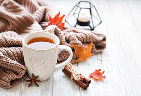 Autumn composition. Cup of tea, women fashion sweaters, dried leaves. Autumn, fall concept.