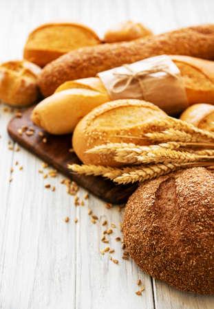 Surtido de pan horneado en madera blanca Foto de archivo
