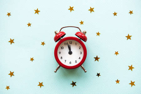 Flat lay Christmas composition with alarm clock and gold stars  on light blue background. 免版税图像