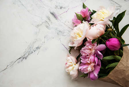 Background with pink peonies on white marble  board