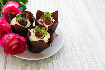 Cupcakes with figs and pink roses on a white wooden background Archivio Fotografico - 133223788