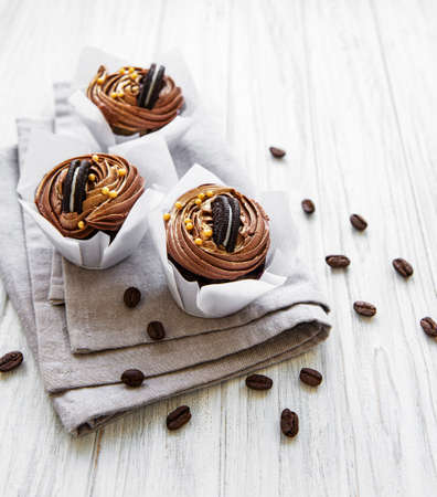 Cupcakes or muffins with chocolate cream  on цршеу цщщвут  background. Holiday cake celebration, delicious dessert, close up Archivio Fotografico - 133226190