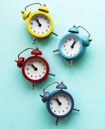 Composición de Navidad laicos plana con relojes de alarma de color sobre fondo azul claro.