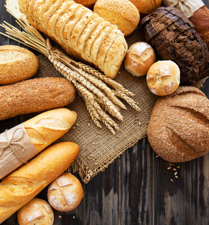 Assortment of baked bread on old wooden background