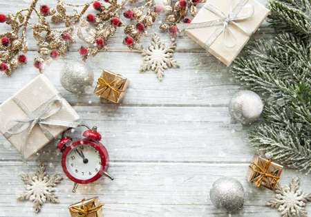 Flat lay composition with alarm clock, pine branches  and Christmas decorations on white wooden background.