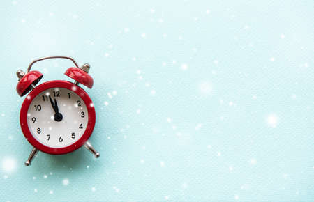 Flat lay Christmas composition with alarm clock and snow on light blue background. Imagens