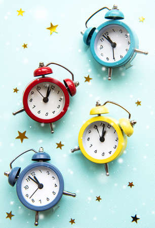 Flat lay Christmas composition with color alarm clocks  and golden stars on light blue background.