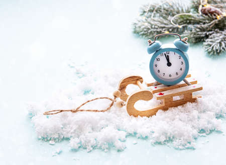 Christmas alarm clock on a wooden sled in the snow shows the time midnight.  Christmas card concept, new year holidays. Imagens