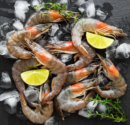 Fresh raw  prawns and spices on  black background