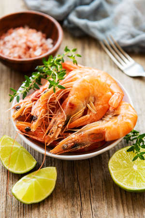Shrimps served with lemons and spices on a old wooden table Imagens
