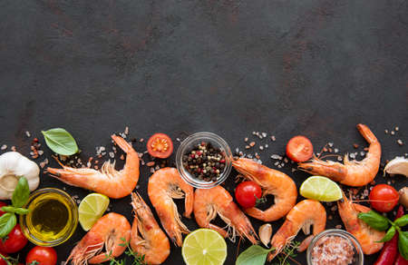 Fresh seafood - shrimps  with vegetables, herbs and spices on black background Imagens