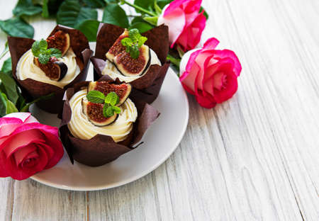 Cupcakes with figs and pink roses on a white wooden background Imagens