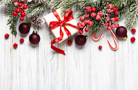 Christmas and New year background with fir branches, holly berry, pine cones and decorations on white wooden background. Creative flat lay, top view design with copy space