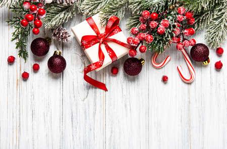 Kerstmis en Nieuwjaar achtergrond met dennentakken, holly berry, dennenappels en decoraties op witte houten achtergrond. Creatief platliggend, bovenaanzichtontwerp met kopieerruimte