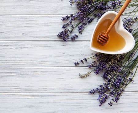 Bowl of liquid honey with lavender on white wooden table, flat lay