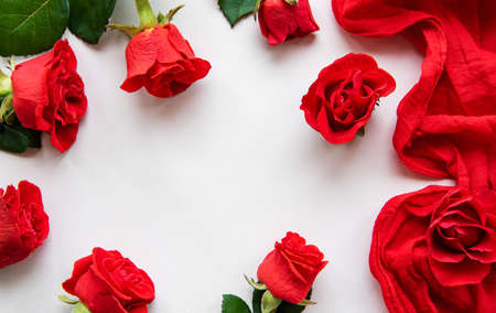 Red roses heads ans scarf scattered on a white background, overhead view. Flat lay Banque d'images