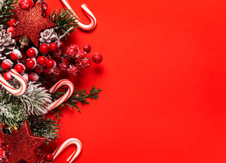 Christmas and New year background with fir branches, holly berry,  pine cones and decorations on red background. Creative flat lay, top view design with copy space