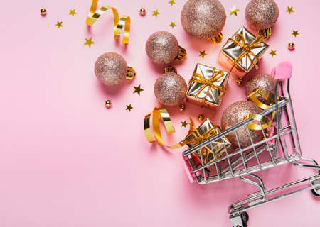 Christmas shopping cart with balls, golden holiday decorations  on pink pastel
