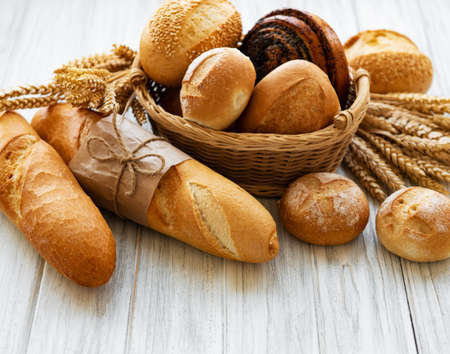 Assortment of baked bread on white wooden background Foto de archivo
