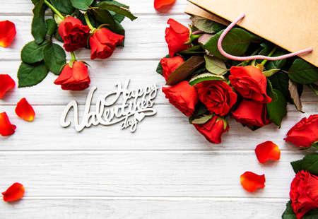 赤いバラで作られたフレーム、白い木製の背景に花びら。フラットレイ、トップビュー、コピースペース。