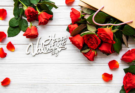Frame made of red roses, petals on white wooden background. Flat lay, top view, copy space.