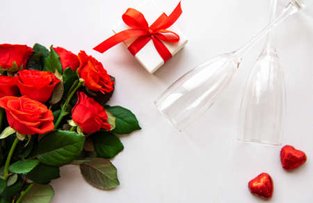Red roses and two glasses on a white