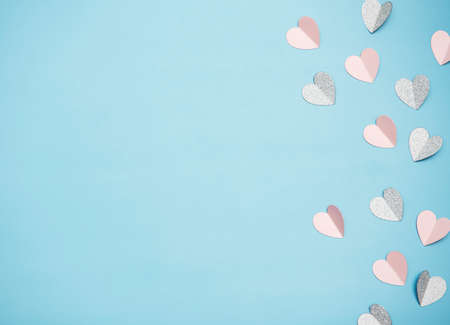 Hearts made of paper on a light blue background, top view. Pink background with hearts for Valentine's day or wedding.