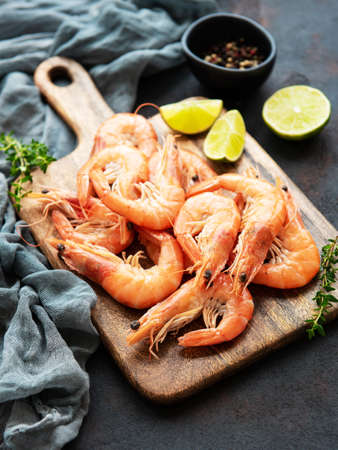 Shrimps served with lemons and spices on a black background